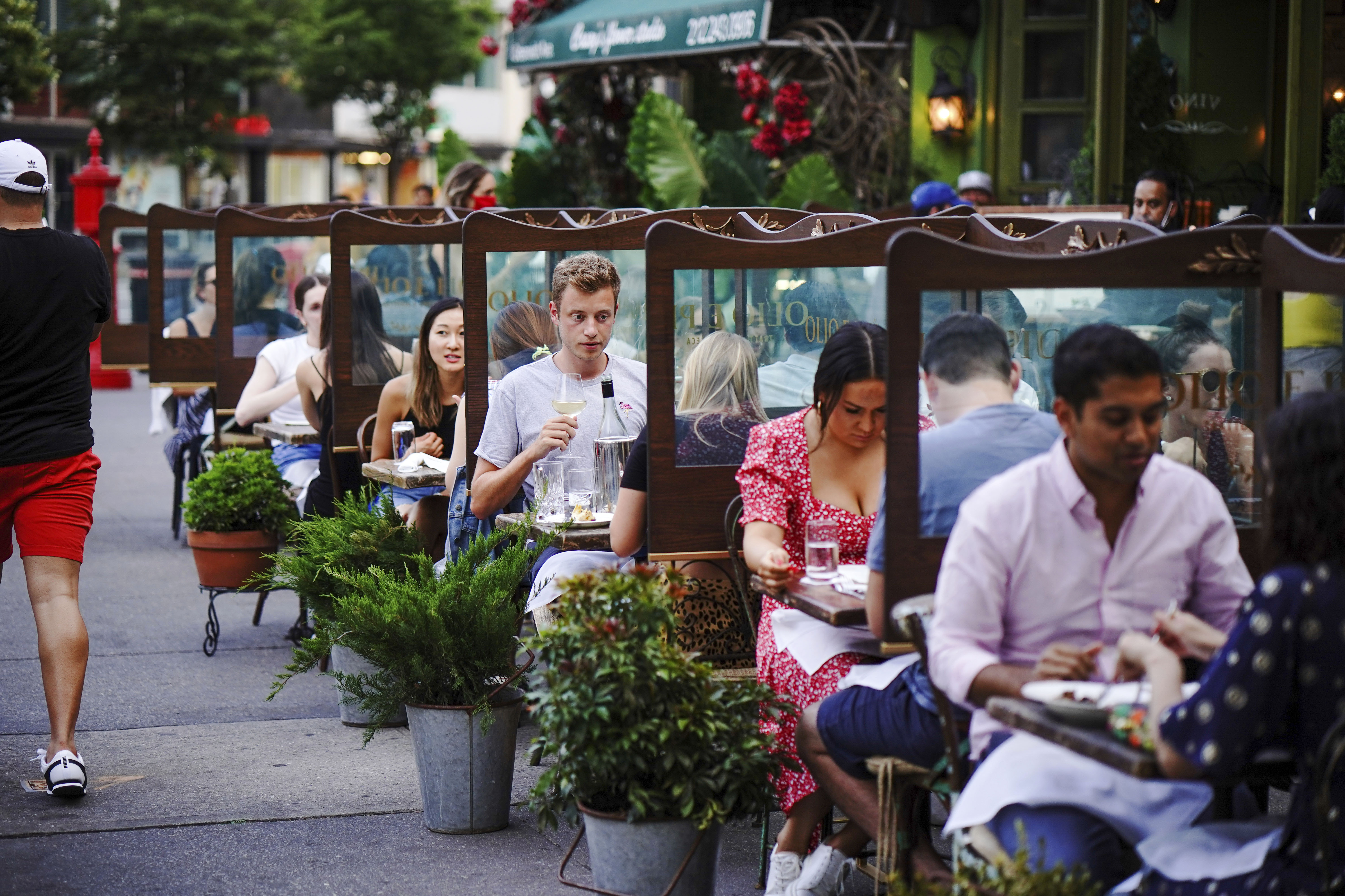 People eat outdoors at a restaurant in New York on June 26.