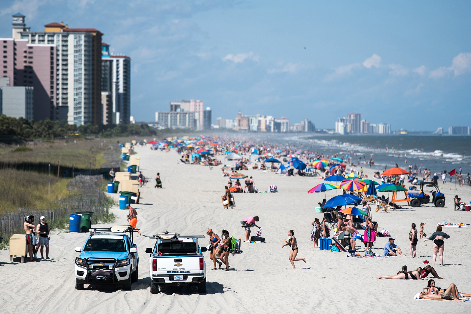 Beach Patrol police officers talk to beach goers from their vehicles in Myrtle Beach, South Carolina, on  May 23.