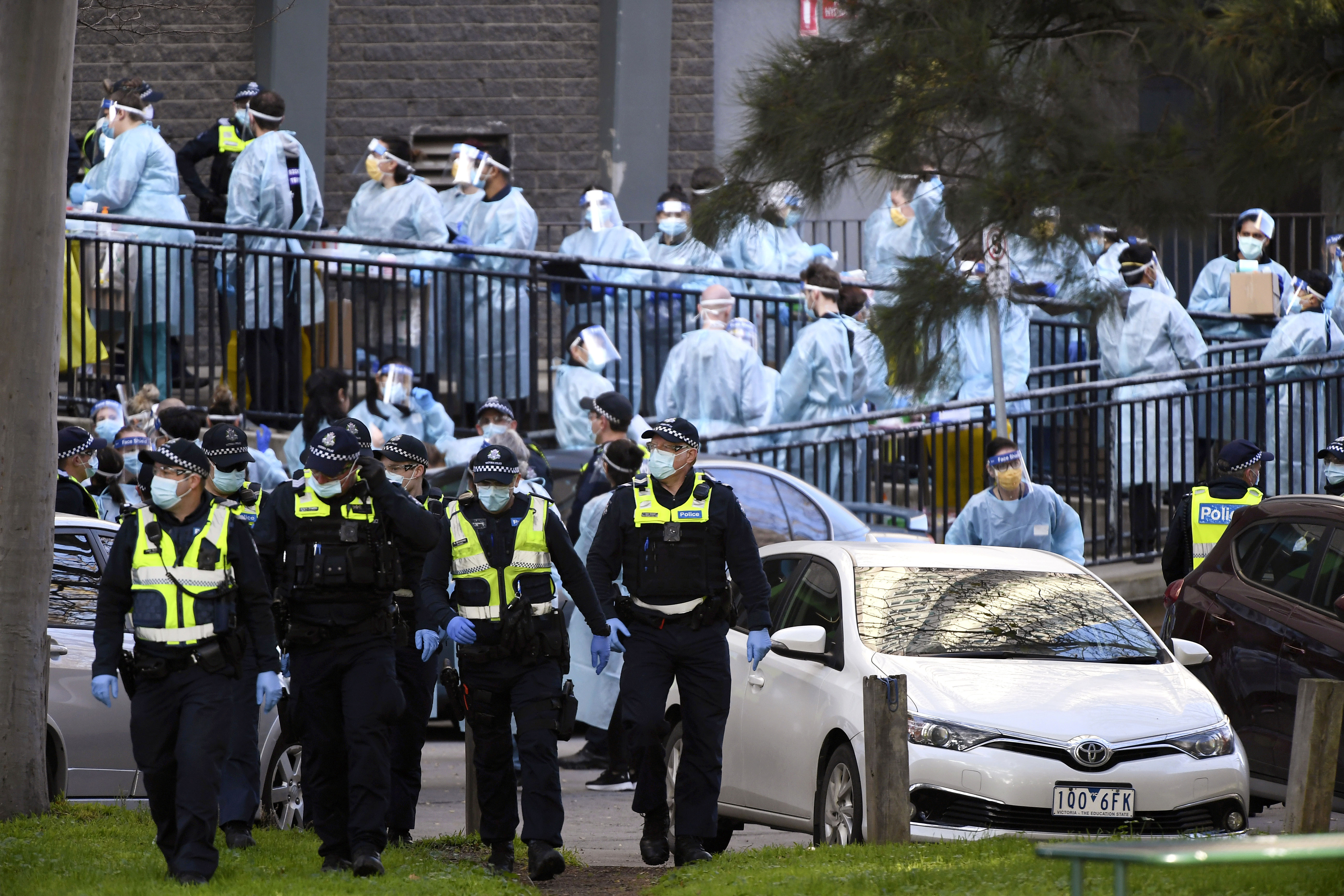 Police officers and health care workers are stationed outside a public housing tower that is locked down in Melbourne on July 8.