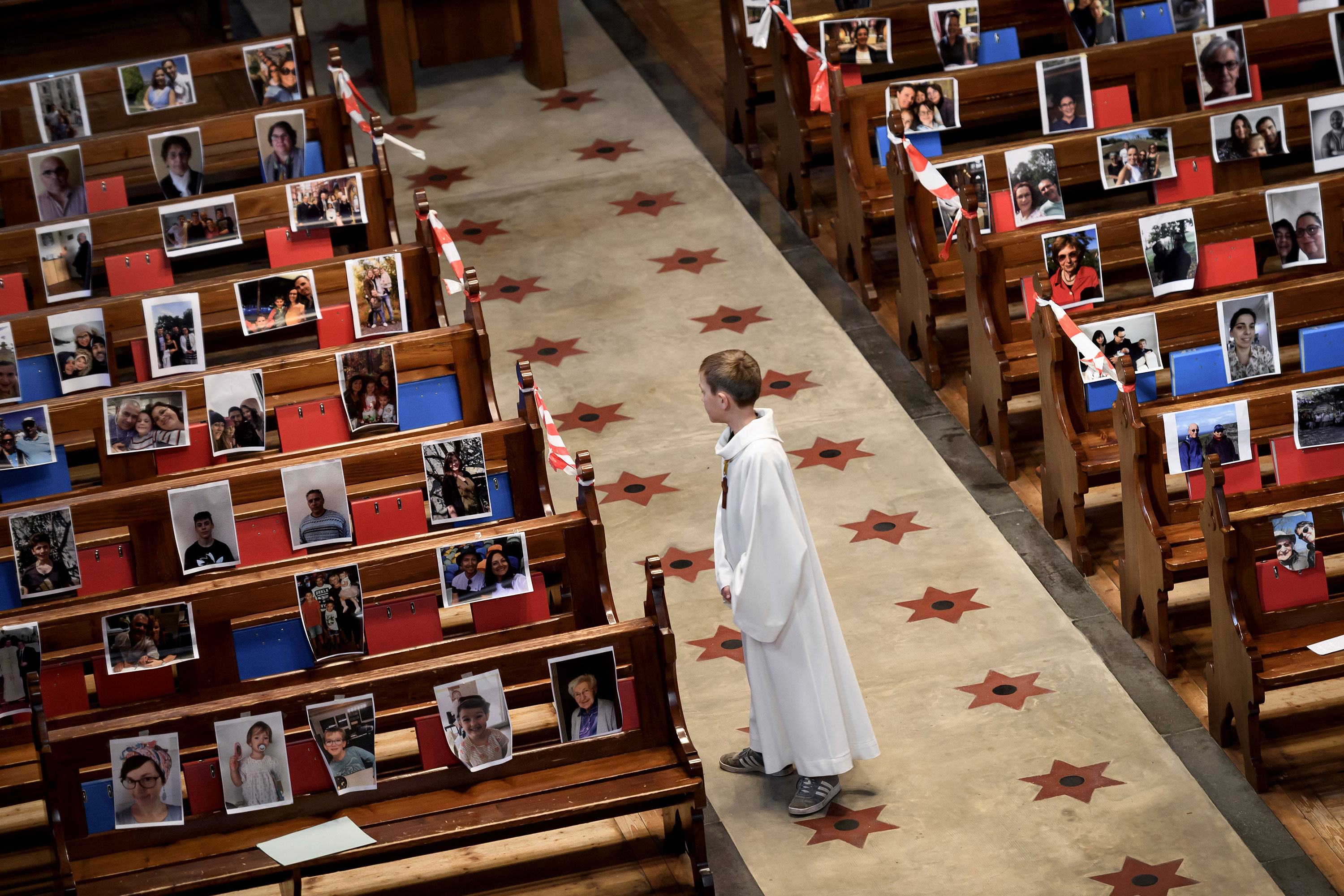 An altar boy stands in the central aisle of the Basilica of Neuchatel which pews display the portraits of 400 parishioners unable to attend the mass due to coronavirus on May 3.