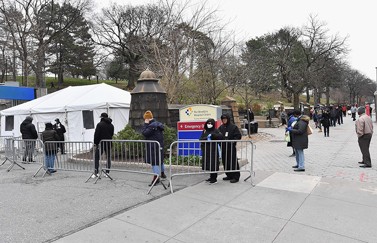 People who believe they have COVID-19 and who meet the criteria wait in line to be pre-screened for the corona virus outside of the Brooklyn Hospital Center on Fridayd, March 20, in the Brooklyn borough of New York.