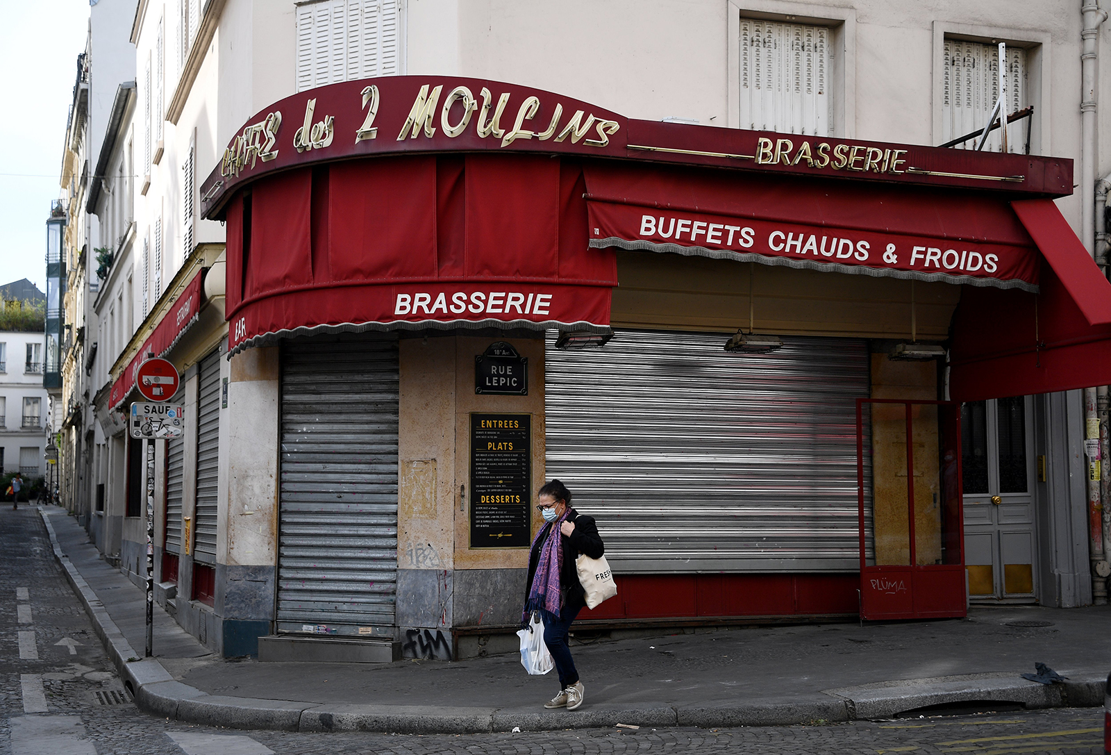 "A woman walks past the entrance of the closed restaurant ""Cafe des 2 Moulins"" in Paris on April 21."