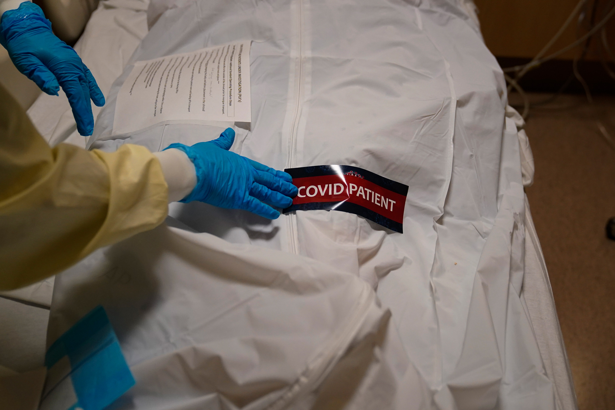 A hospital worker places a sticker on a body bag holding a deceased patient at Providence Holy Cross Medical Center in Los Angeles on January 9.