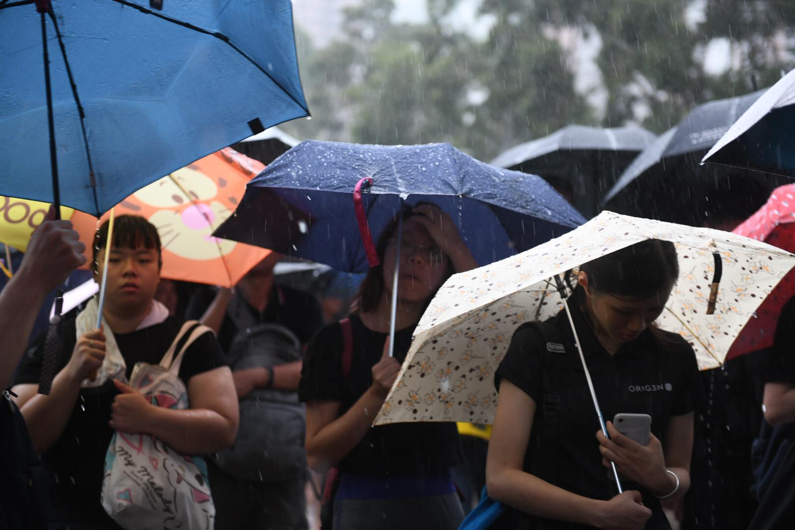 Protesters huddle under umbrellas in Victoria Park in Hong Kong.