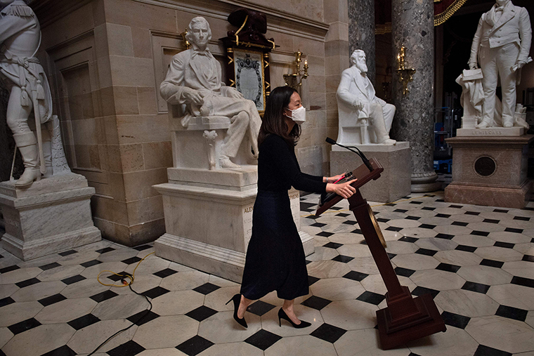A staff member moves Speaker of the House Nancy Pelosi's lectern on  Wednesday, January 13, in Washington, DC.