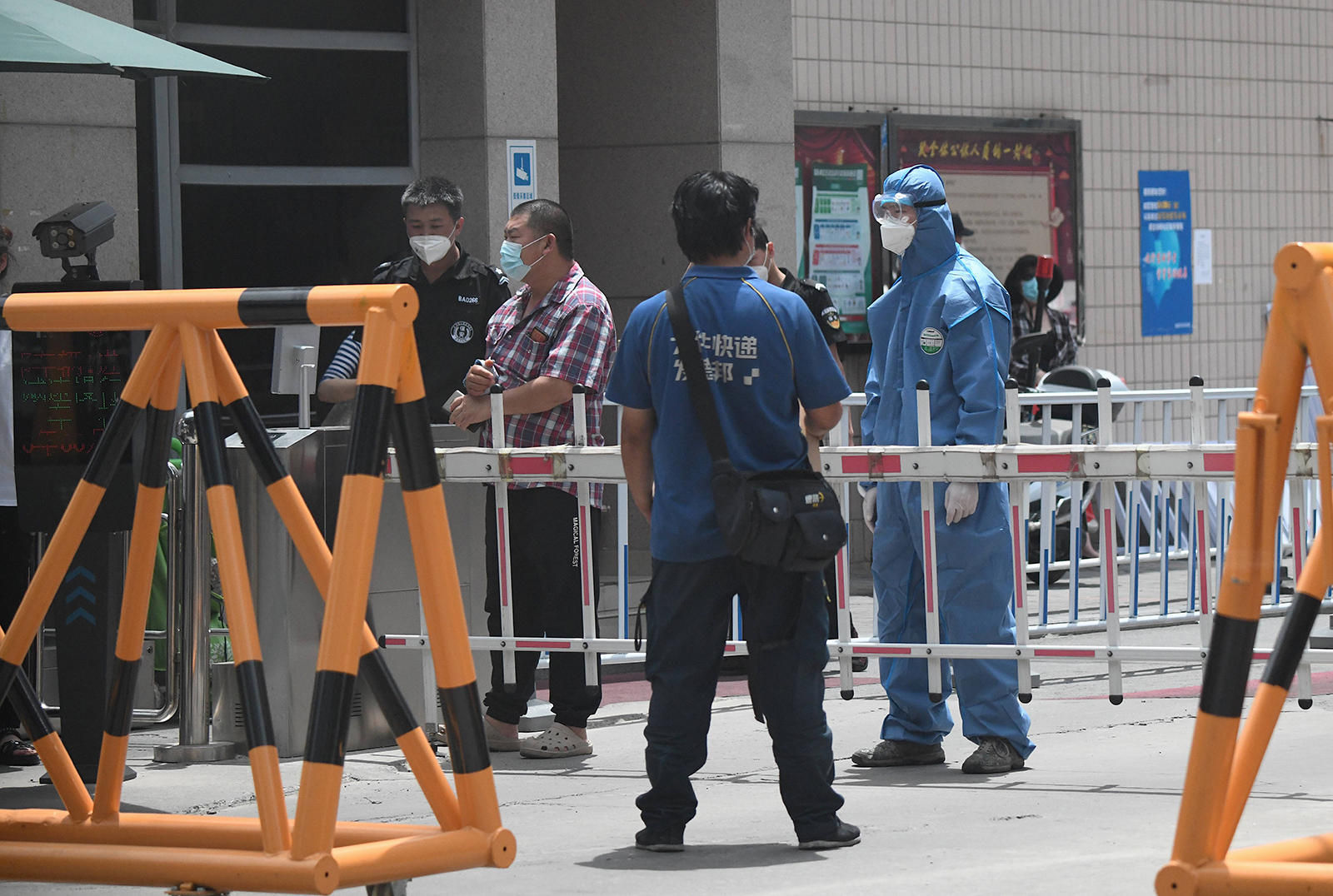 A security personnel wearing a protective suit stands guard at a residential area under lockdown near Yuquan East Market in Beijing on June 15.