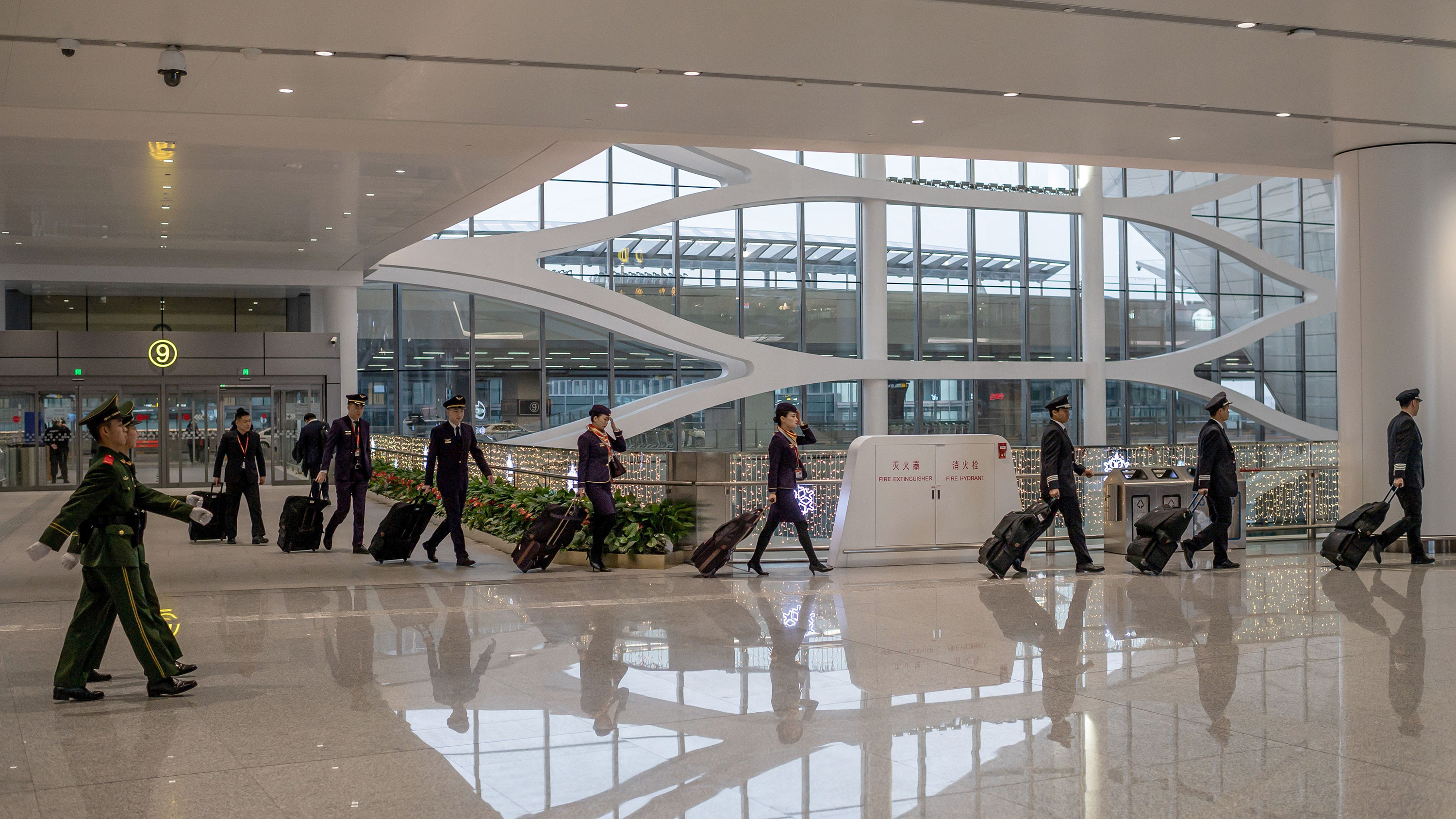 An airline crew enters the Beijing Daxing International Airport on January 21.