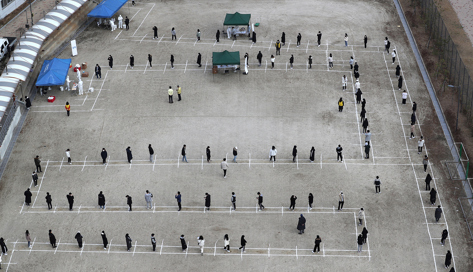 High school students and staff wait in line to take coronavirus tests at a makeshift clinic set up on a playground of a school in Sejong, South Korea, on Friday, Nov. 27.