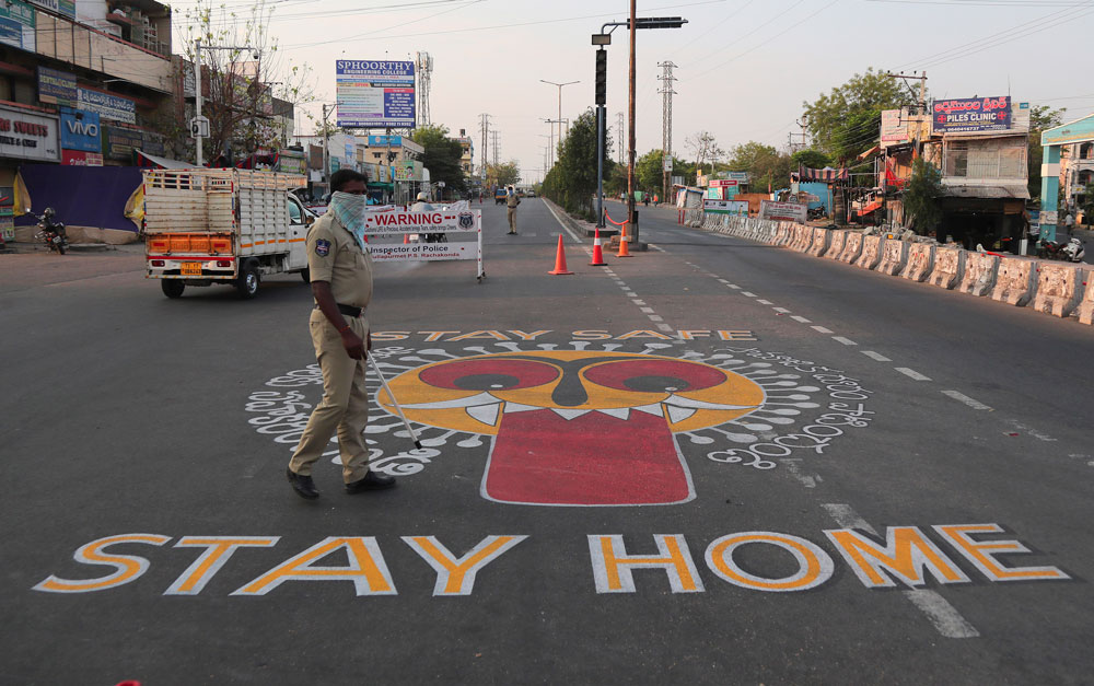 An Indian policeman walks past an art work displayed on a road urging people to stay home during lockdown in Hyderabad.