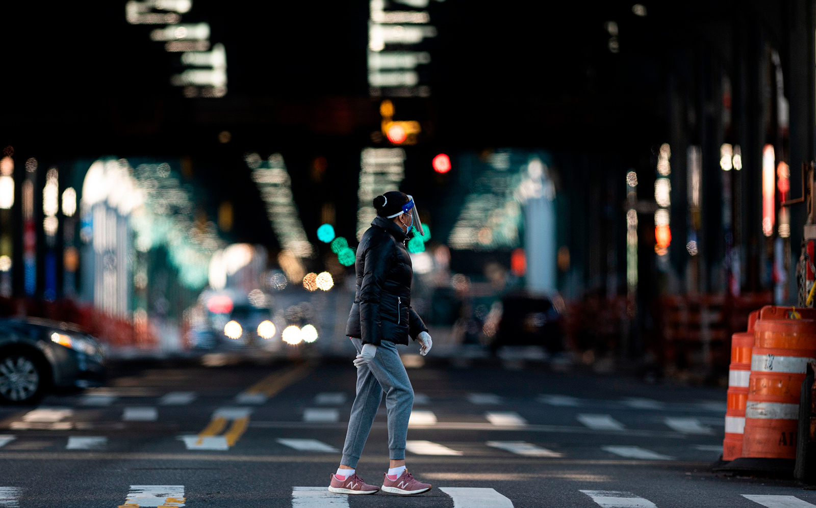 A person wearing a face shield and a mask walks in the streets in the Jackson Heights neighborhood of Queens on April 28, in New York City.