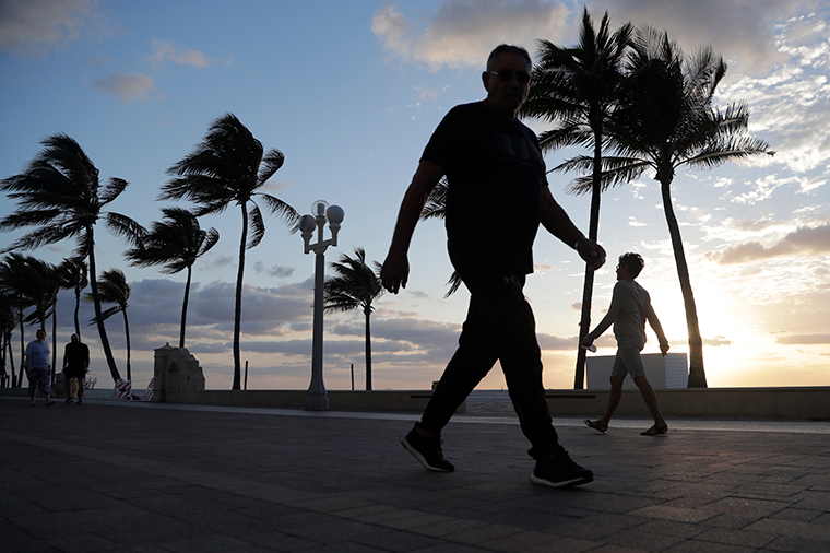 People walk along the Hollywood Beach Broadwalk at sunrise on May 13, in Hollywood, Florida.