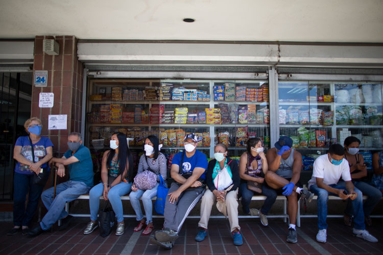 Customers wait to go into a supermarket in Caracas, Venezuela, Monday, March 16.