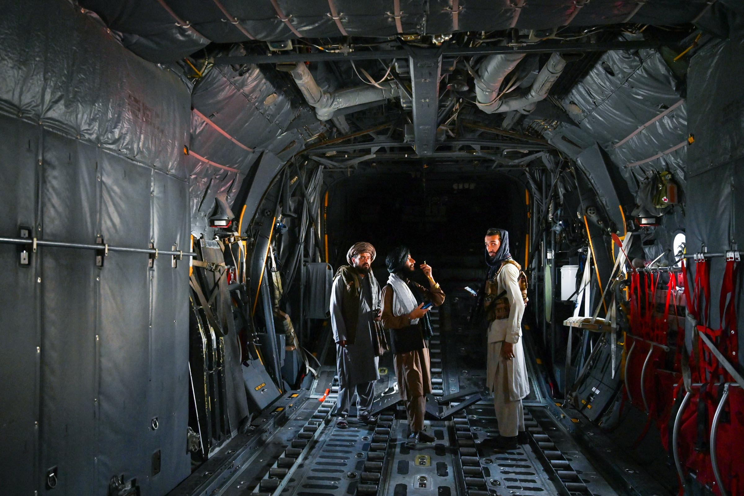 Members of the Taliban stand inside an Afghan Air Force aircraft at the airport.