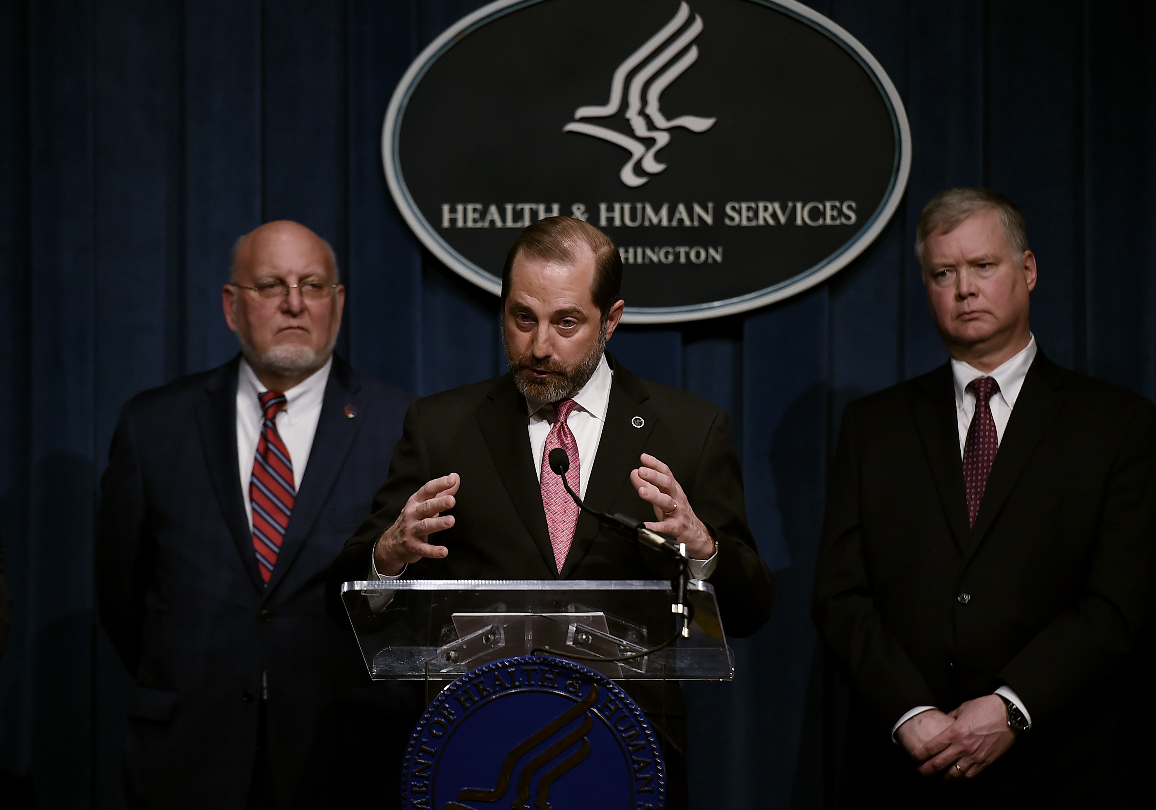 US Health and Human Services Secretary Alex Azar speaks as Centers for Disease Control and Prevention (CDC) Director Robert R. Redfield (left) and Deputy Secretary of State Stephen Biegun (right) listen during a news conference on Friday in Washington.