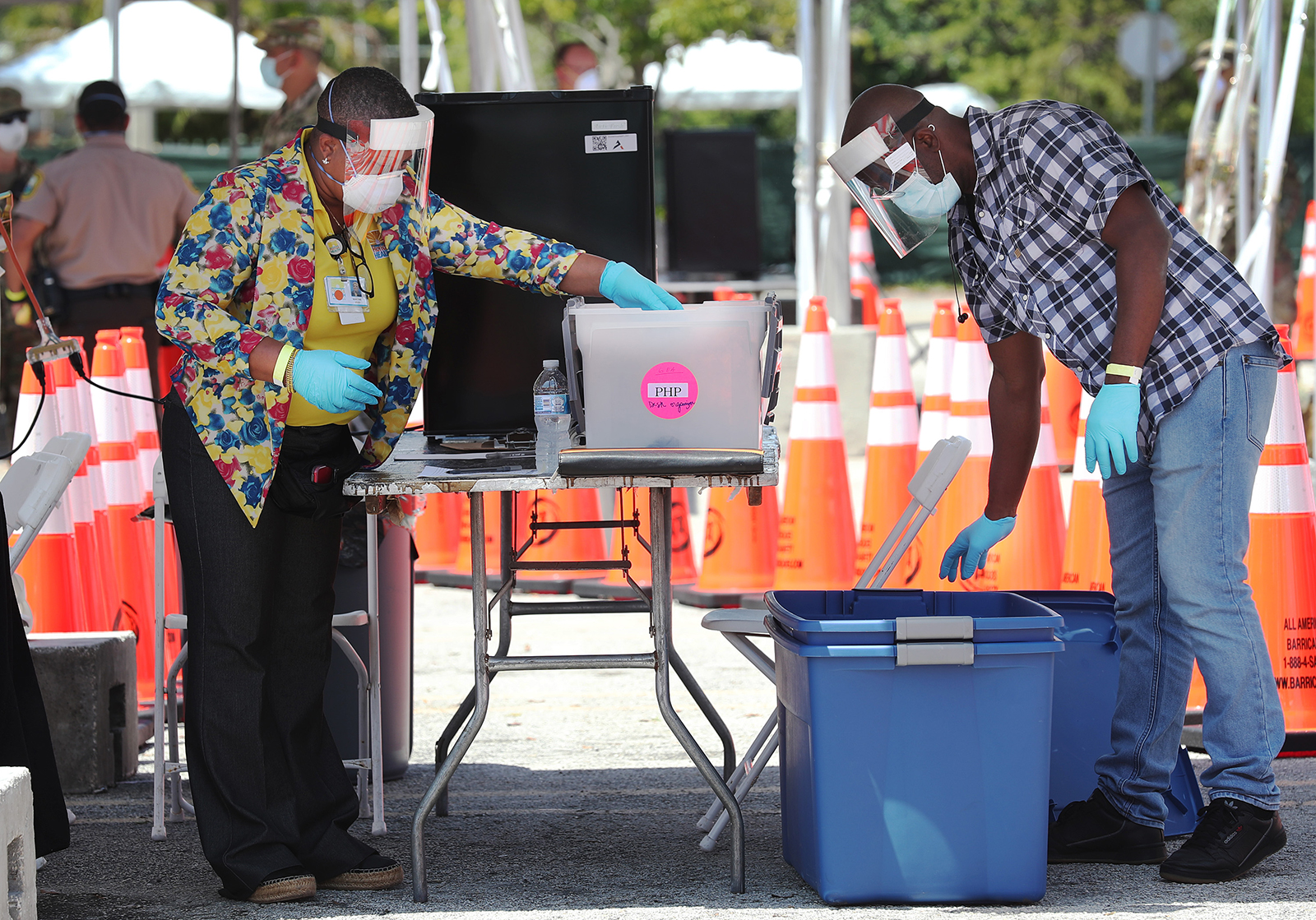 Health care workers wait for people to arrive to be tested at the Covid-19 walk up testing site that opened on April 27, in North Miami, Florida.