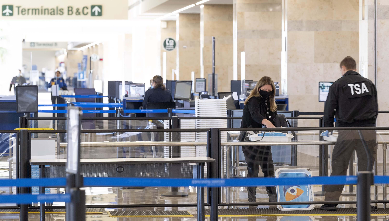 A TSA agent assists a traveler through a security checkpoint at John Wayne Airport in Santa Ana, California, on January 26.