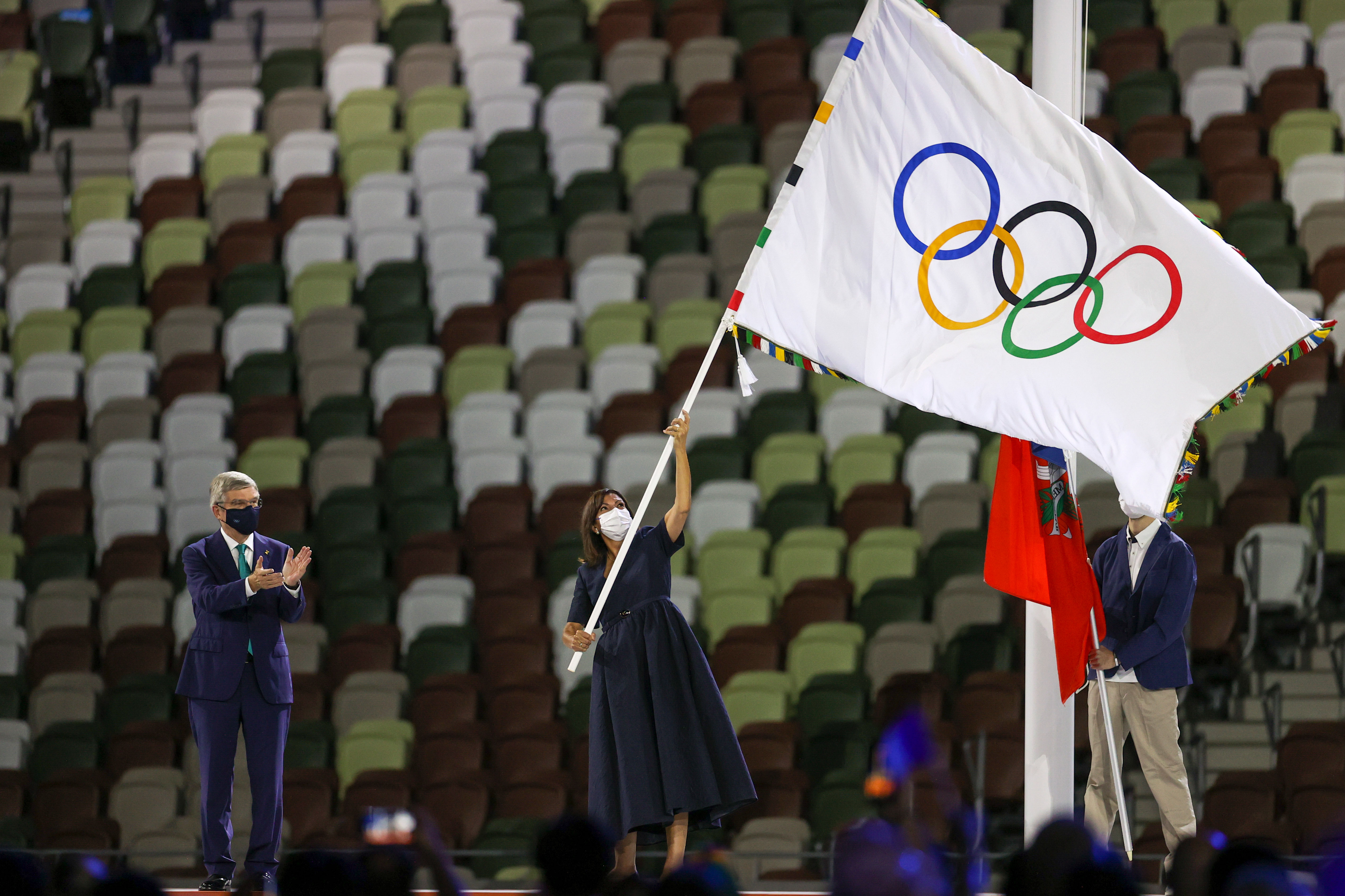 Paris Mayor Anne Hidalgo waves the Olympic flag.