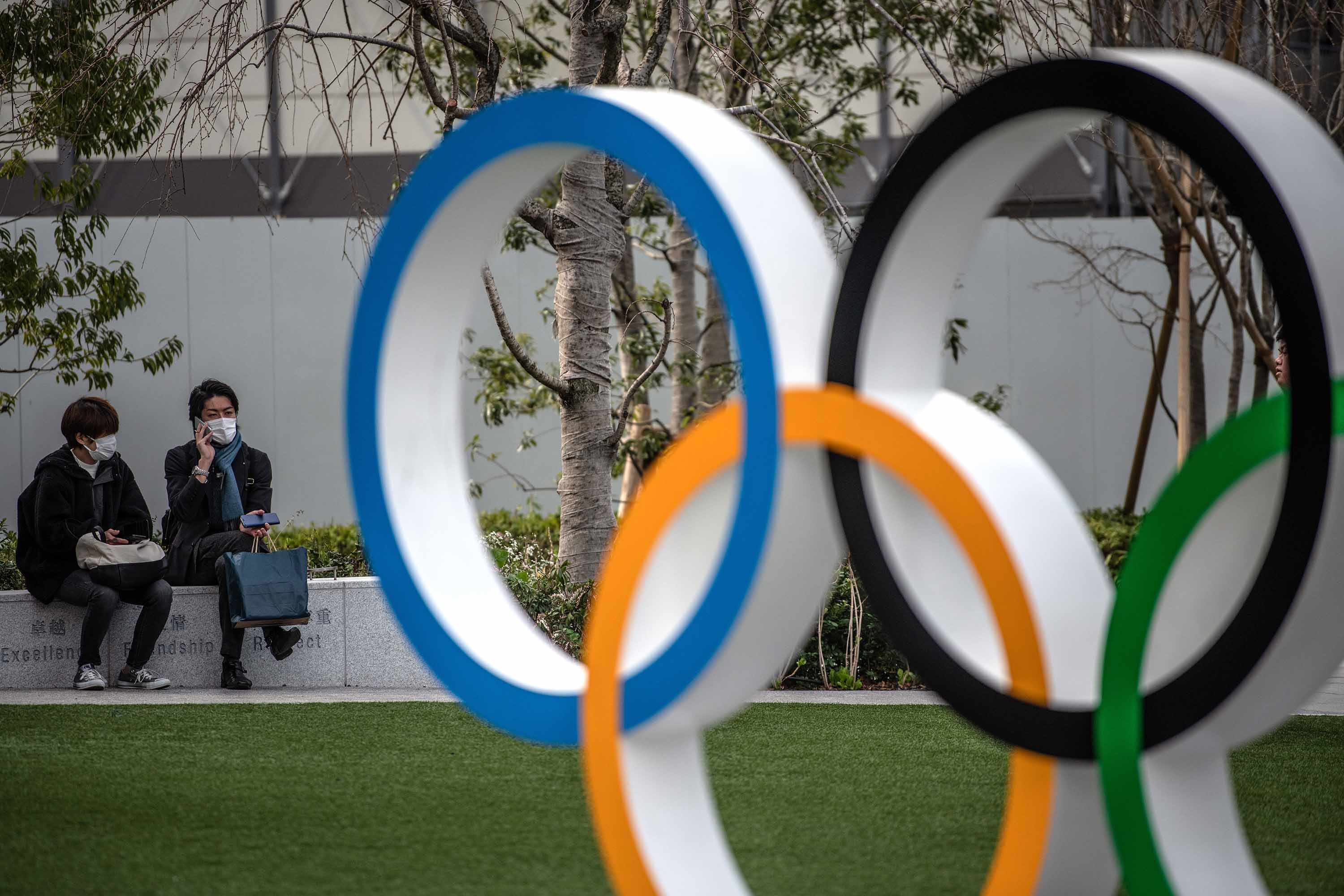 People wearing face masks are pictured next to the Olympic Rings on March 13 in Tokyo, Japan.