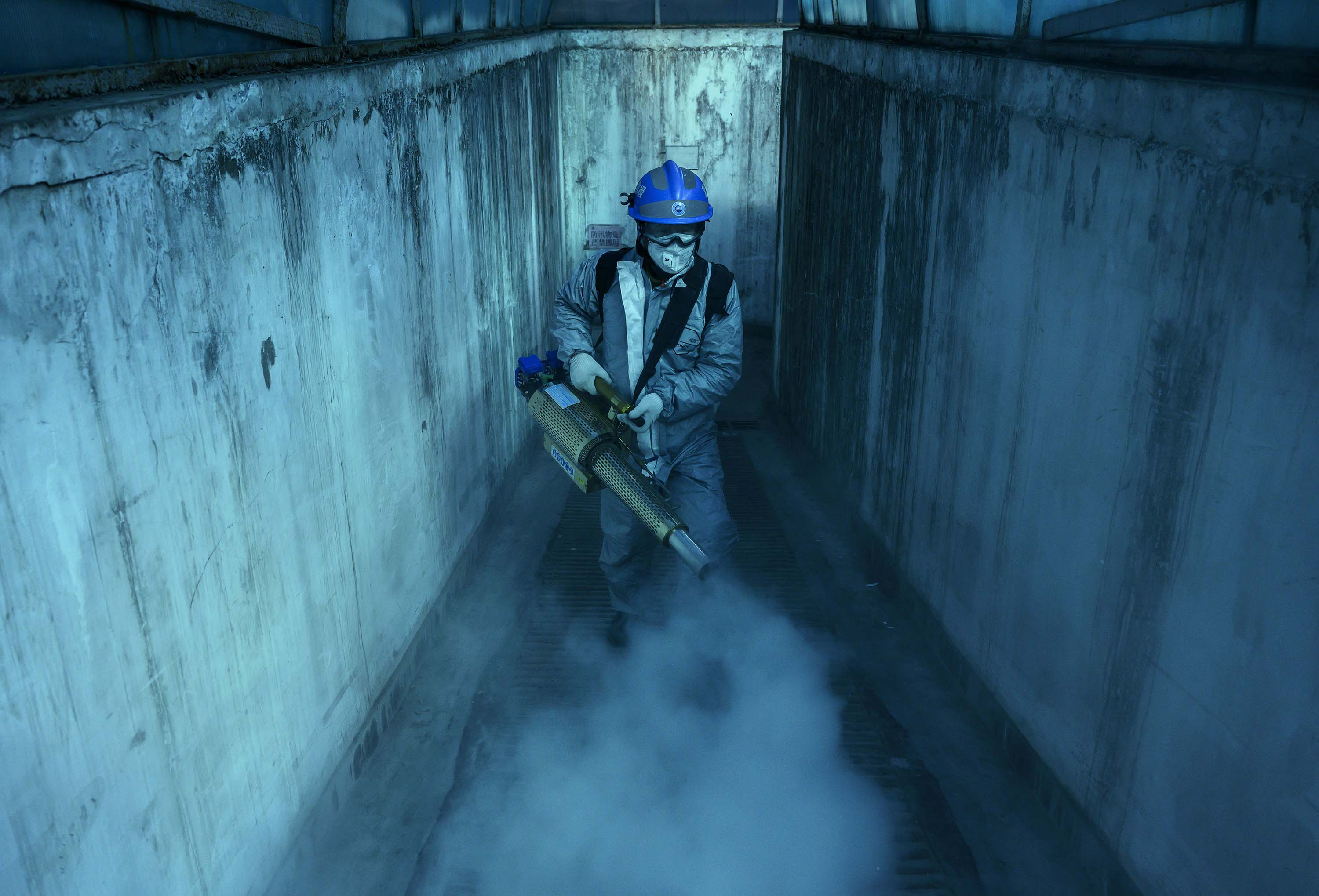 A volunteer from Blue Sky Rescue uses fumigation equipment to disinfect common areas of a local residential compound in Beijing, China on March 5.