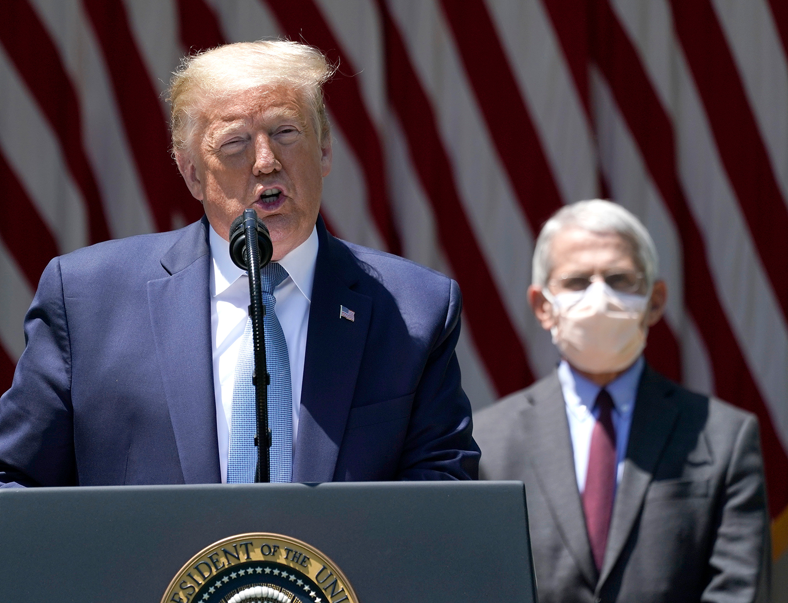 US President Donald Trump is flanked by Dr. Anthony Fauci, director of the National Institute of Allergy and Infectious Diseases while speaking about coronavirus vaccine development in the Rose Garden of the White House on May 15 in Washington.