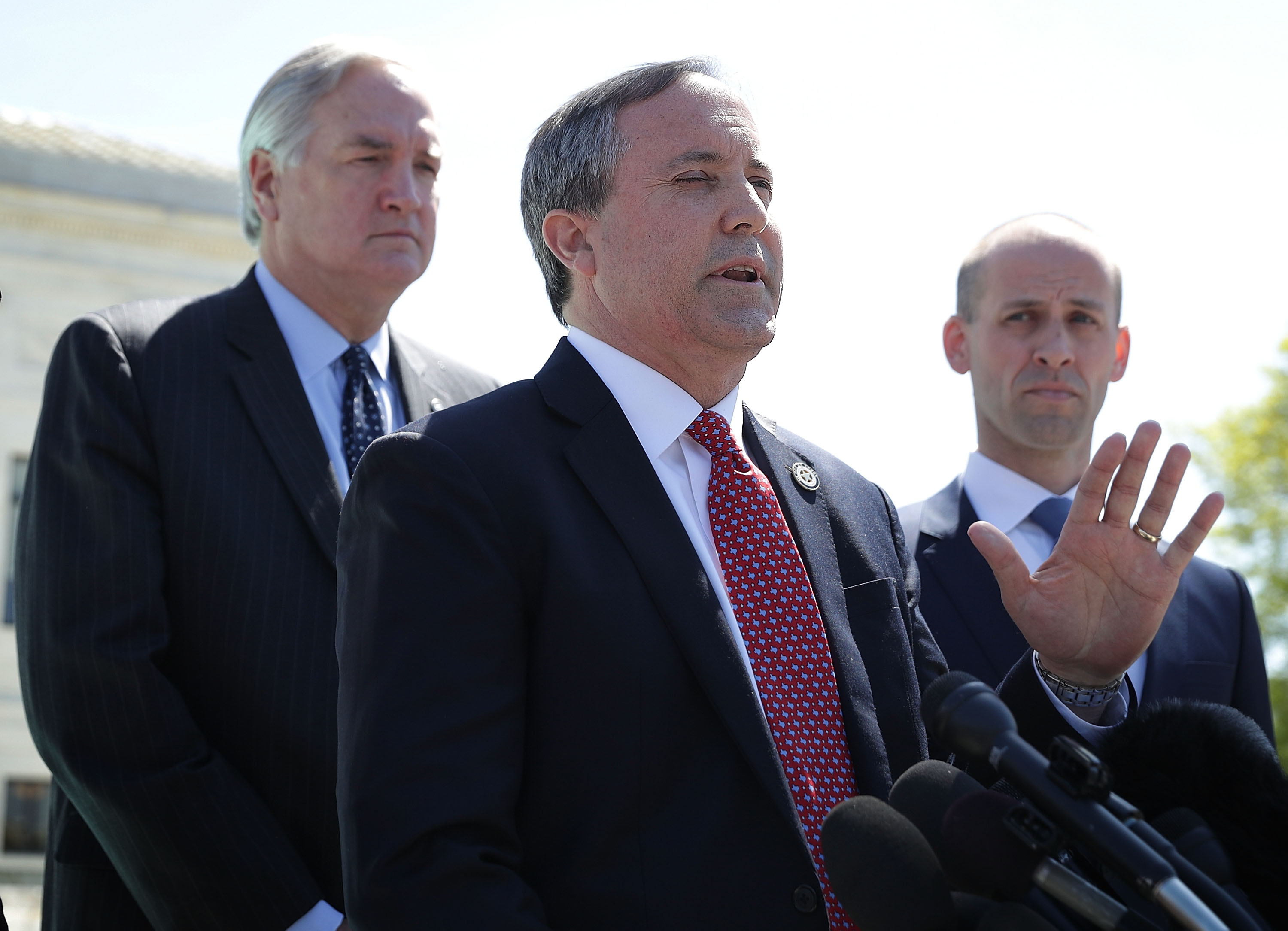 Texas Attorney General Kenneth Paxton (2nd R) speaks to members of the media as former Texas Solicitor General Scott Keller (R) listens in front of the US Supreme Court April 18, 2016 in Washington, DC