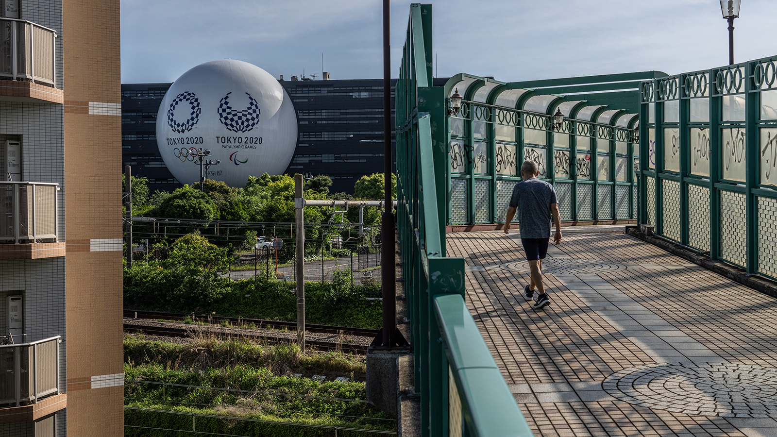 A man passes over a bridge next to a huge semi-sphere bearing the Tokyo Olympics and Paralympics logos on the side of a driving school building on May 6 in Tokyo.