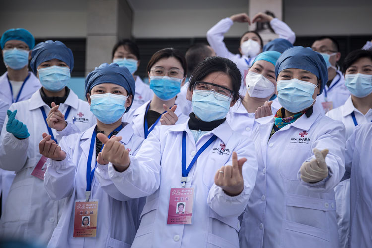 Medical professionals pose for photos as the last batch of coronavirus patients are discharged from Wuchang Fang Cang makeshift hospital on March 10, in Wuhan, Hubei province, China.