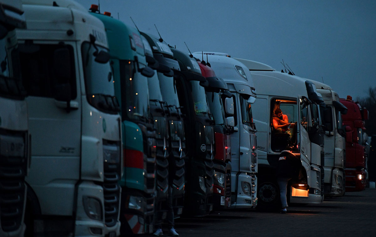 Drivers of freight lorries and heavy goods vehicles are illuminated by the lights inside their cabs as they are parked at a truck stop off the M20 leading to Dover, near Folkestone in Kent, south east England on December 22.