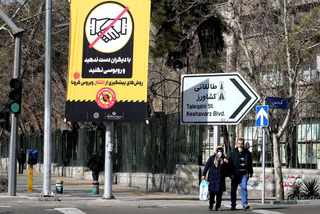 Iranians walk under a coronavirus prevention poster on Wednesday in Tehran, Iran.