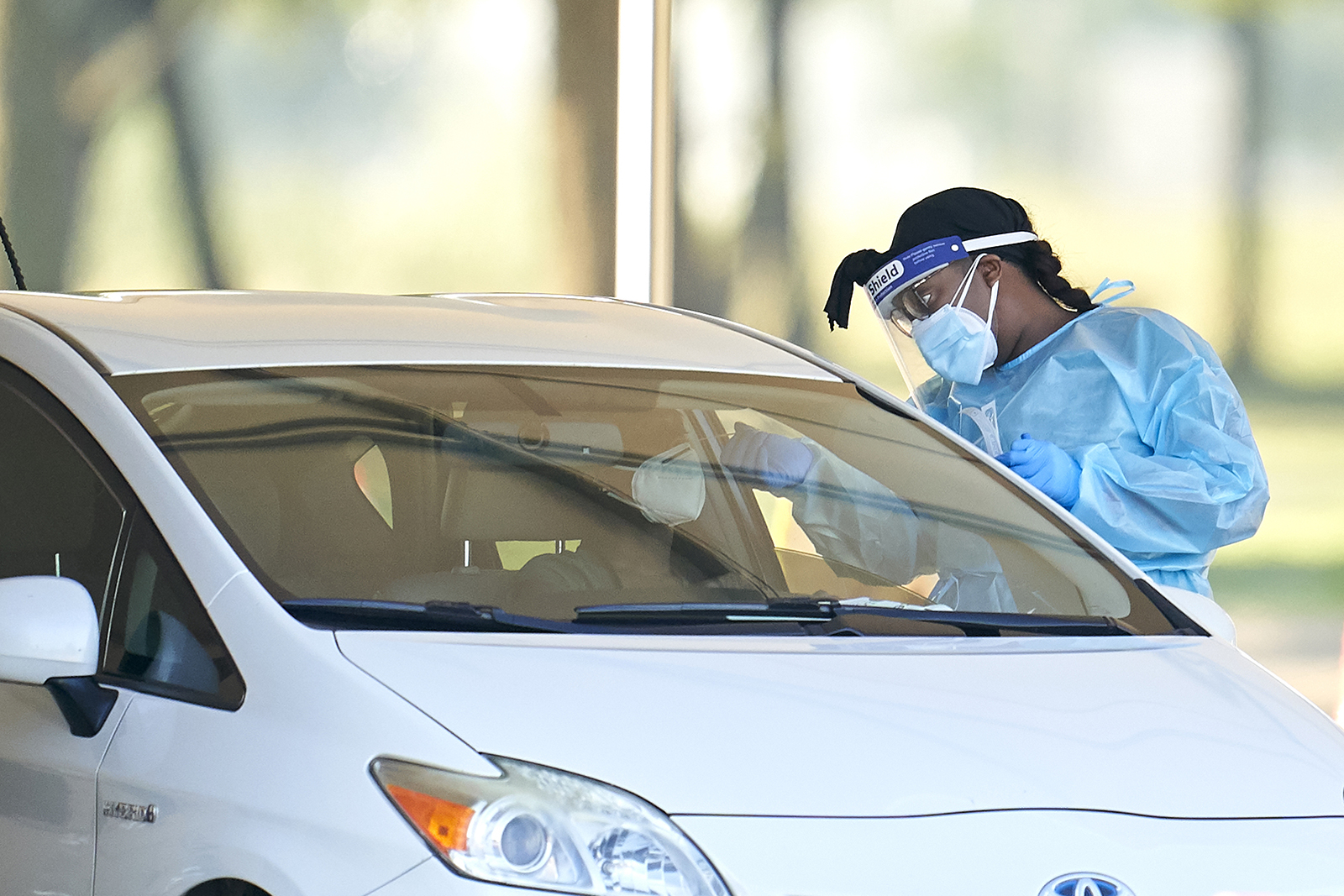 A healthcare worker performs a swab test on a person at a Covid-19 drive-through testing site in Mesquite, Texas, on Tuesday, August 18.