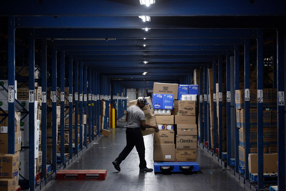 A worker loads boxes onto a pallet at a Kroger Co. grocery distribution center in Louisville, Kentucky, on March 20.