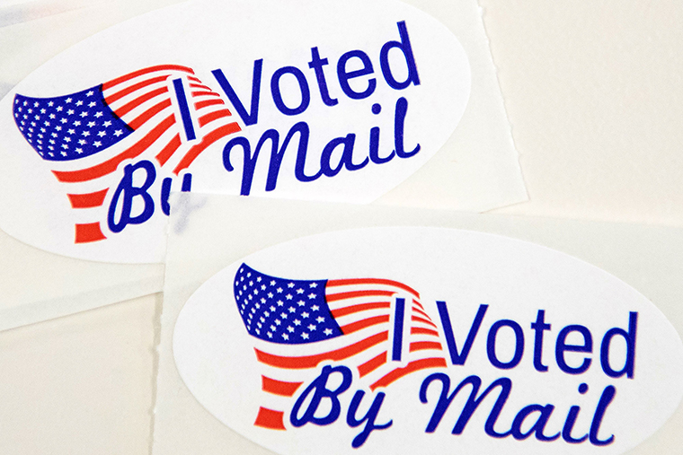 """Stickers that read """"I Voted By Mail"""" sit on a table waiting to be stuffed into envelopes by absentee ballot election workers at the Mecklenburg County Board of Elections office in Charlotte, North Carolina, on September 4."""