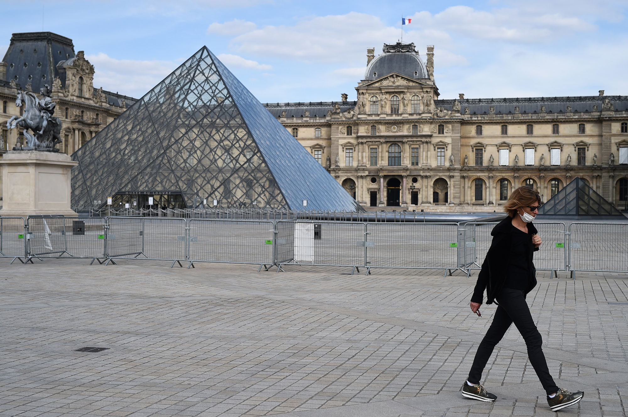 A woman walks in front of the Louvre museum on May 13 in Paris.