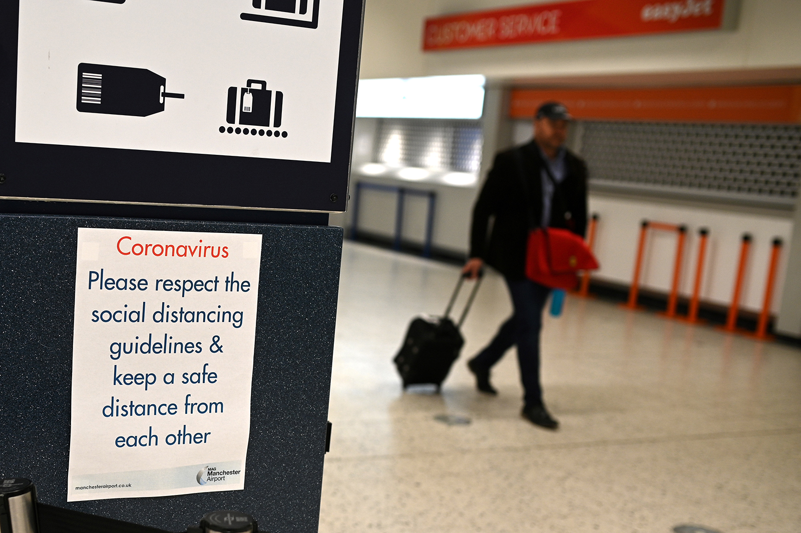 A passenger passes a sign reminding travelers to observe social distancing guidelines at almost-empty check-in desks in the departure hall at Terminal 1 of Manchester Airport in Manchester, England on May 11.