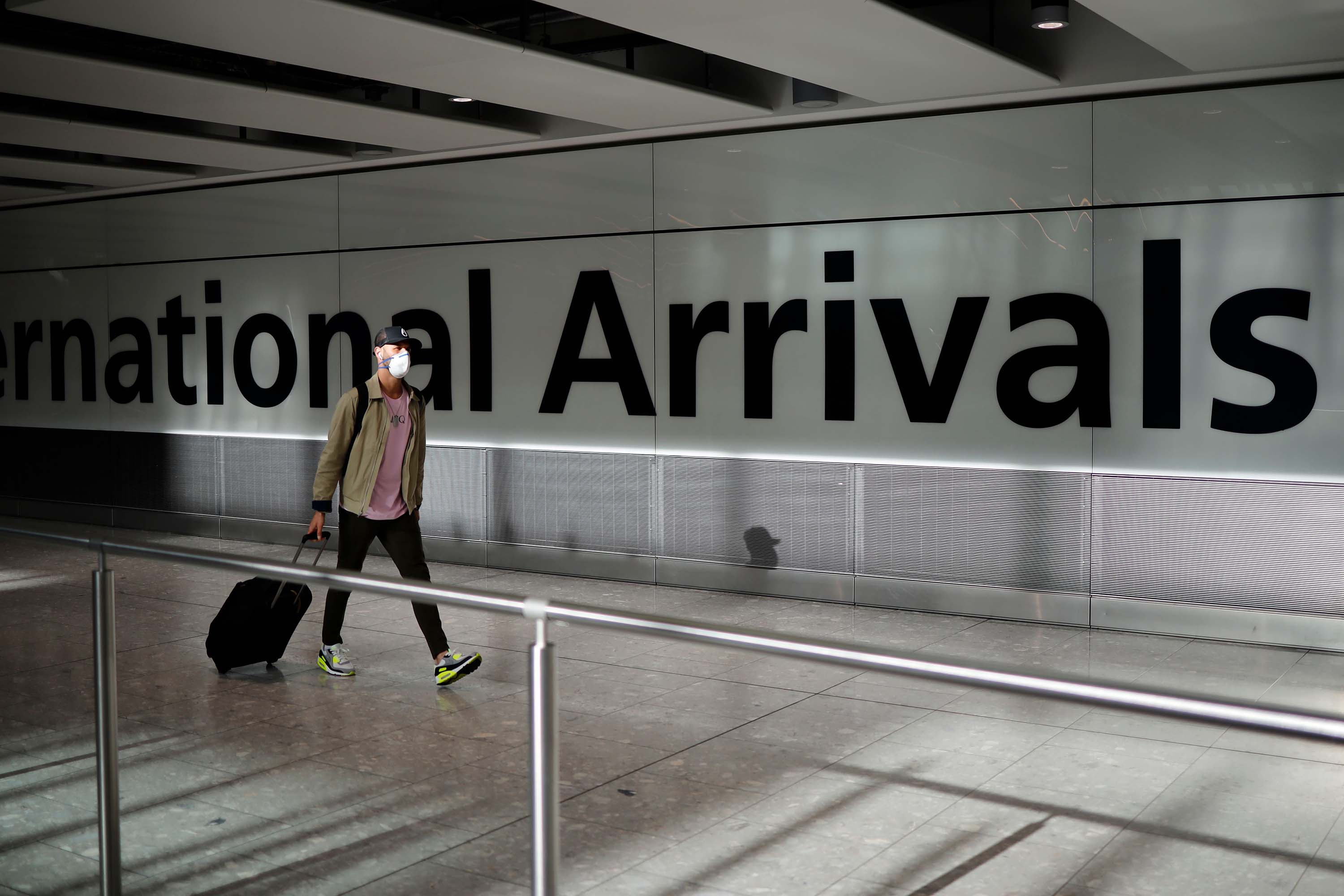 A passenger wearing a face mask arrives at Heathrow airport in west London on May 22.
