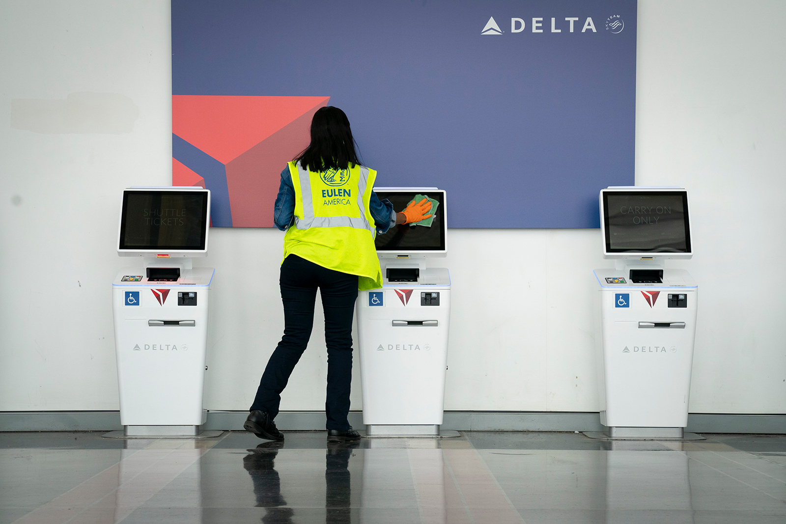 A worker cleans the screens at a Delta self check-in kiosk at Ronald Reagan Washington National Airport, on May 5, in Arlington, Virginia.