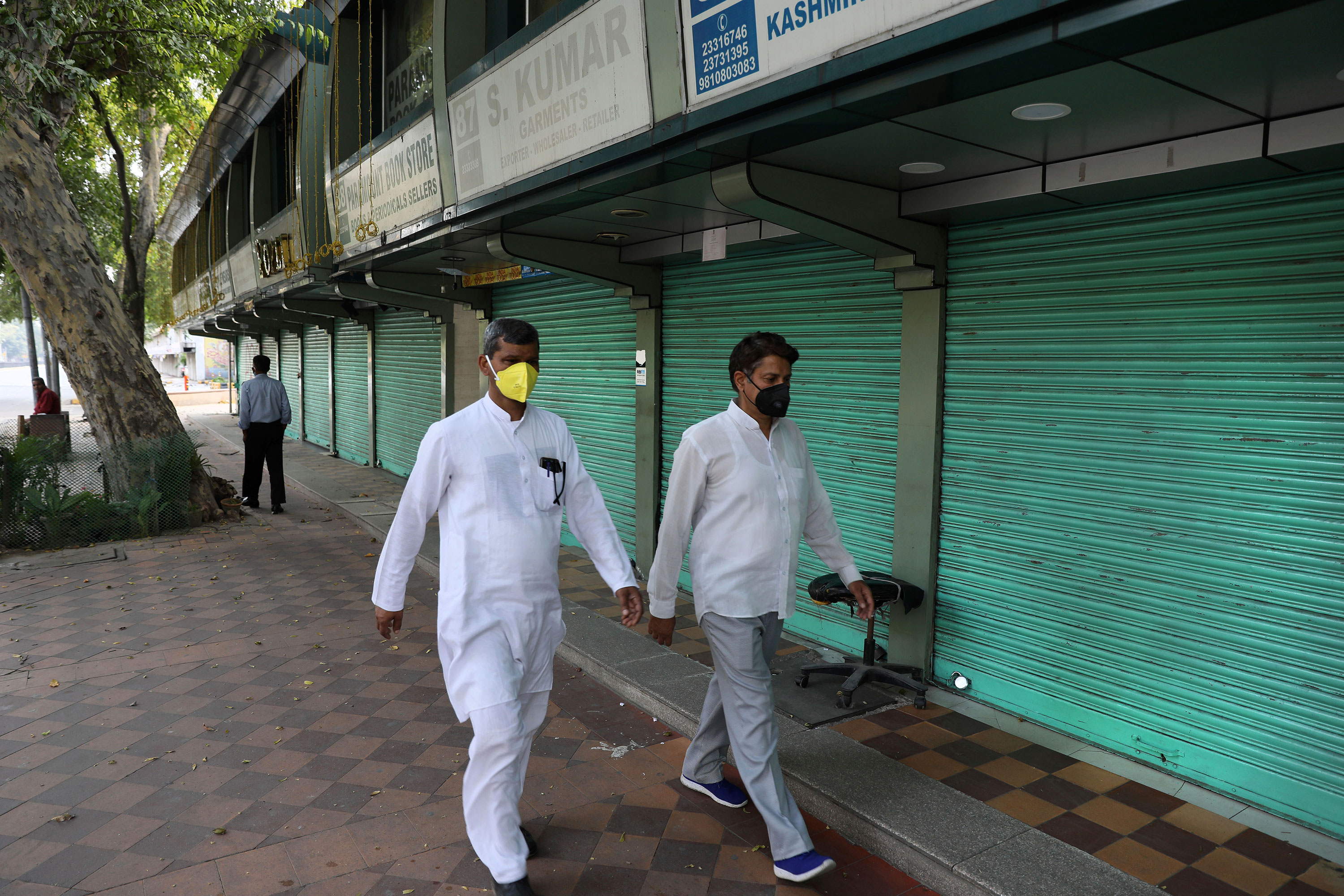 People walk past closed shops in New Delhi on March 23, the first day of the lockdown.