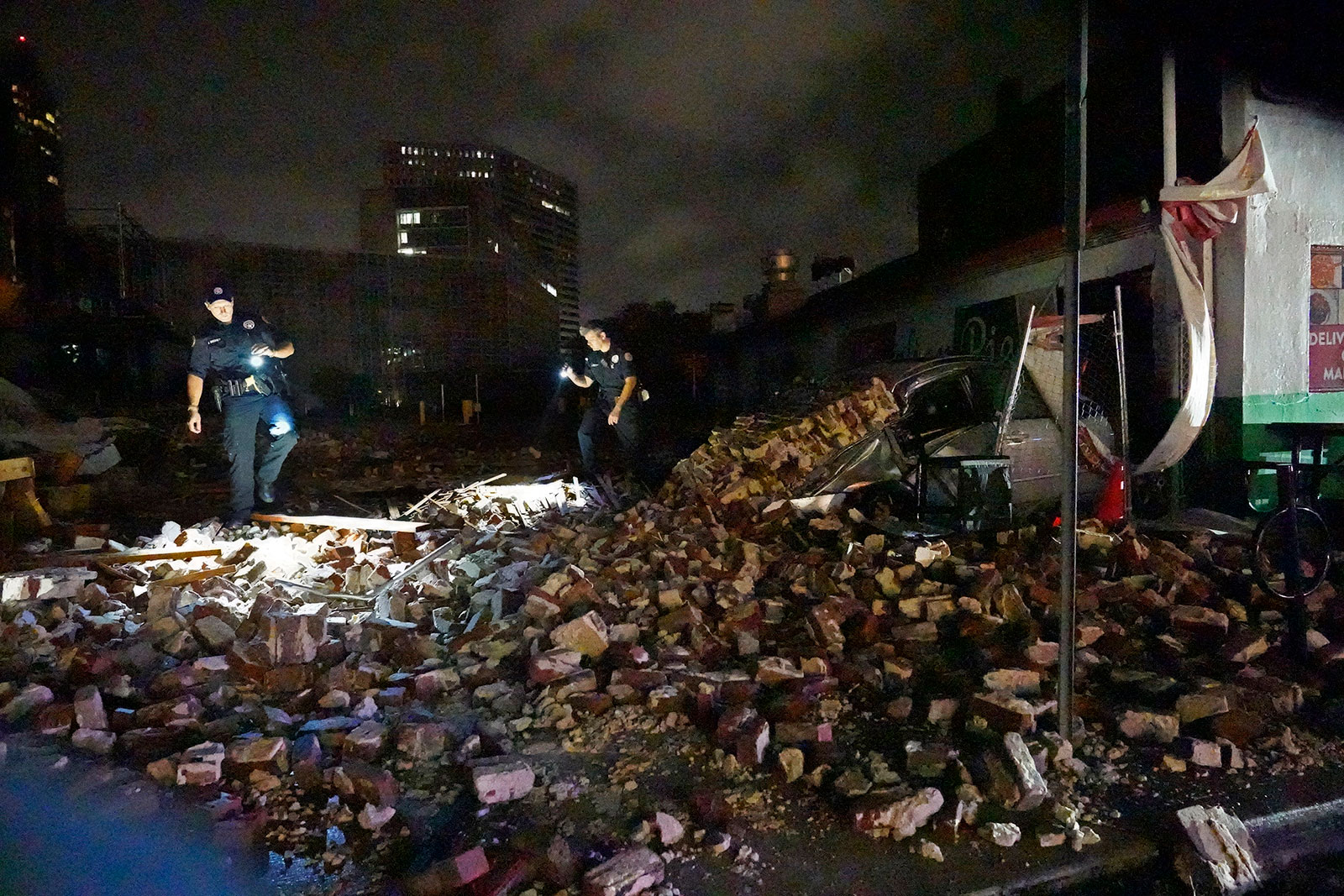 New Orleans Police detectives Adam Buckner, left, and Alexander Reiter, look through debris from a collapsed building in New Orleans on August 30.