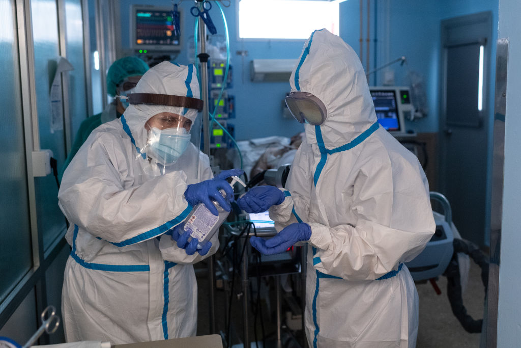 Healthcare staff in protective suits disinfect as they leave a section of the ICU of the Hospital Universitari de Bellvitge on April 09, in L´Hospitalet del Llobregat, near Barcelona, Spain.