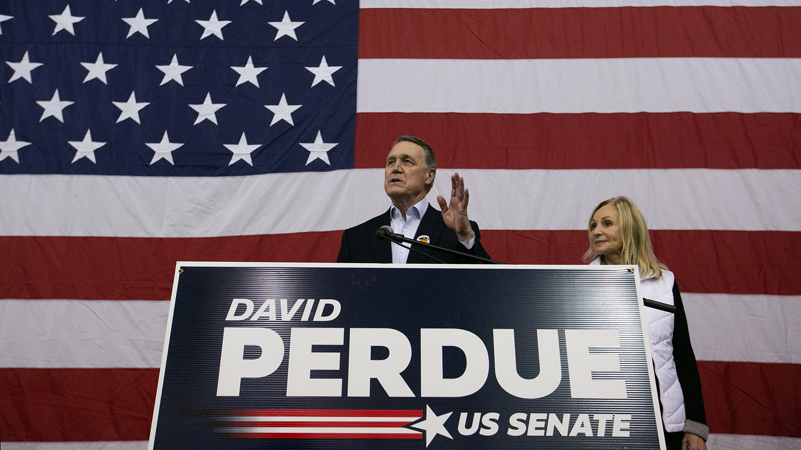 Sen. David Perdue and his wife, Bonnie, address the crowd during a campaign rally at Peachtree Dekalb Airport on December 14, in Atlanta.