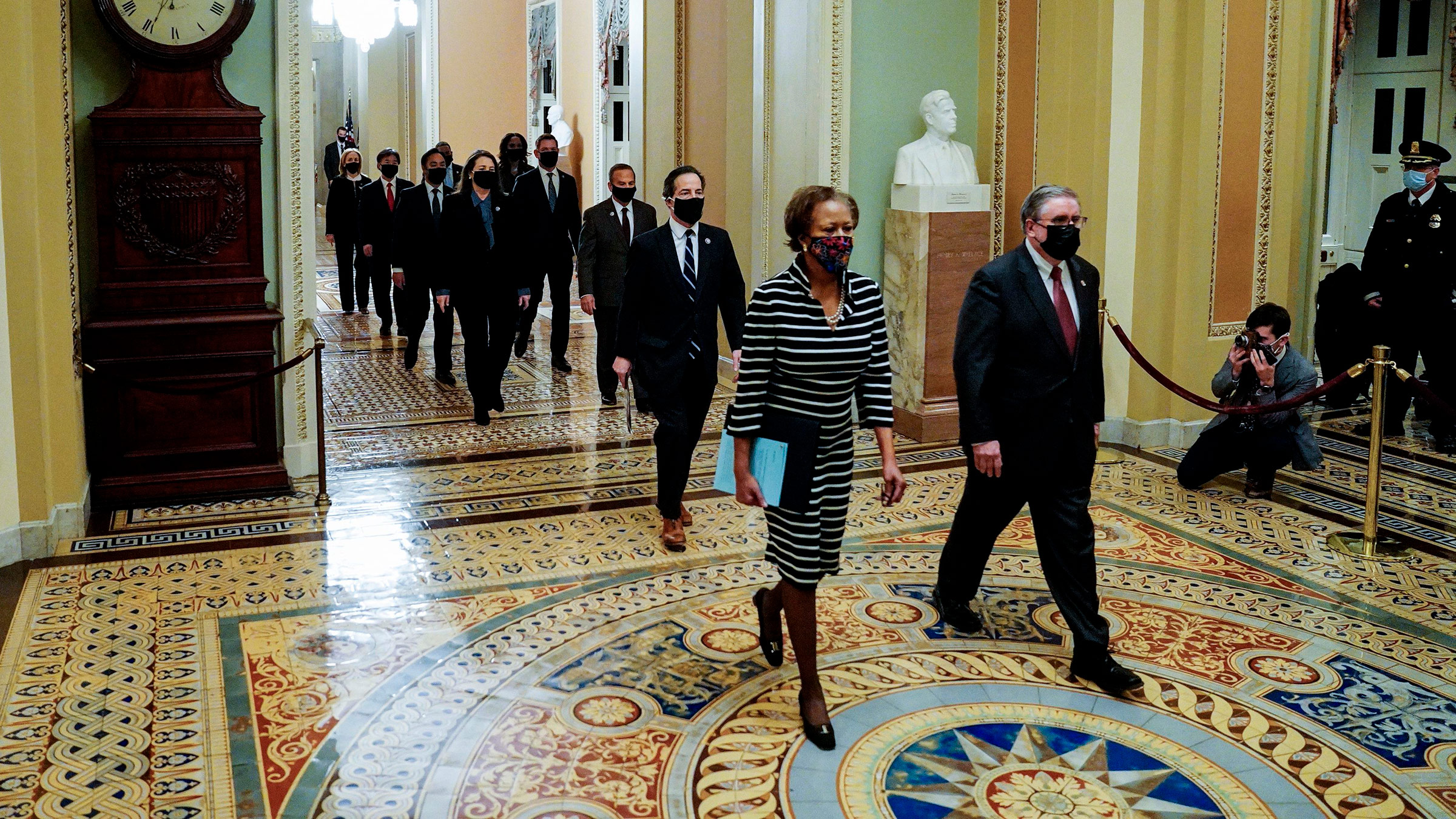 House impeachment managers are lead through the Capitol to deliver the article of impeachment against former President Donald Trump to the Senate floor on January 25, in Washington, DC.