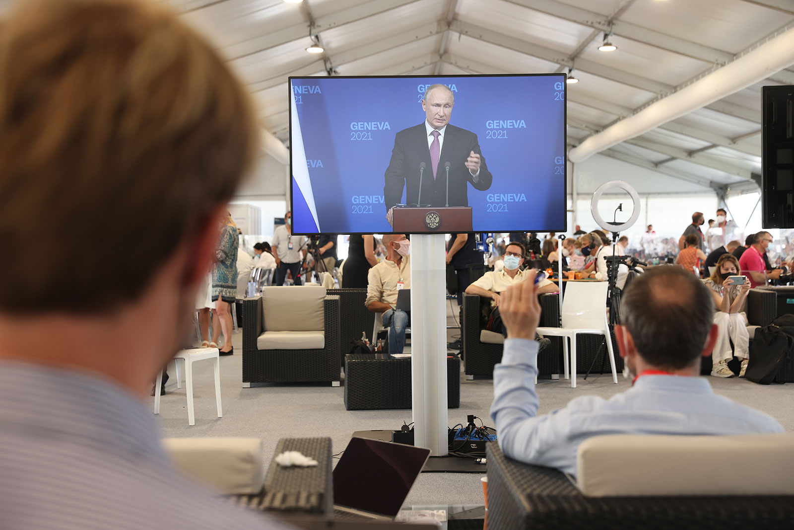 Journalists watch Russian President Vladimir Putin speak during a press conference from a media center in Geneva.