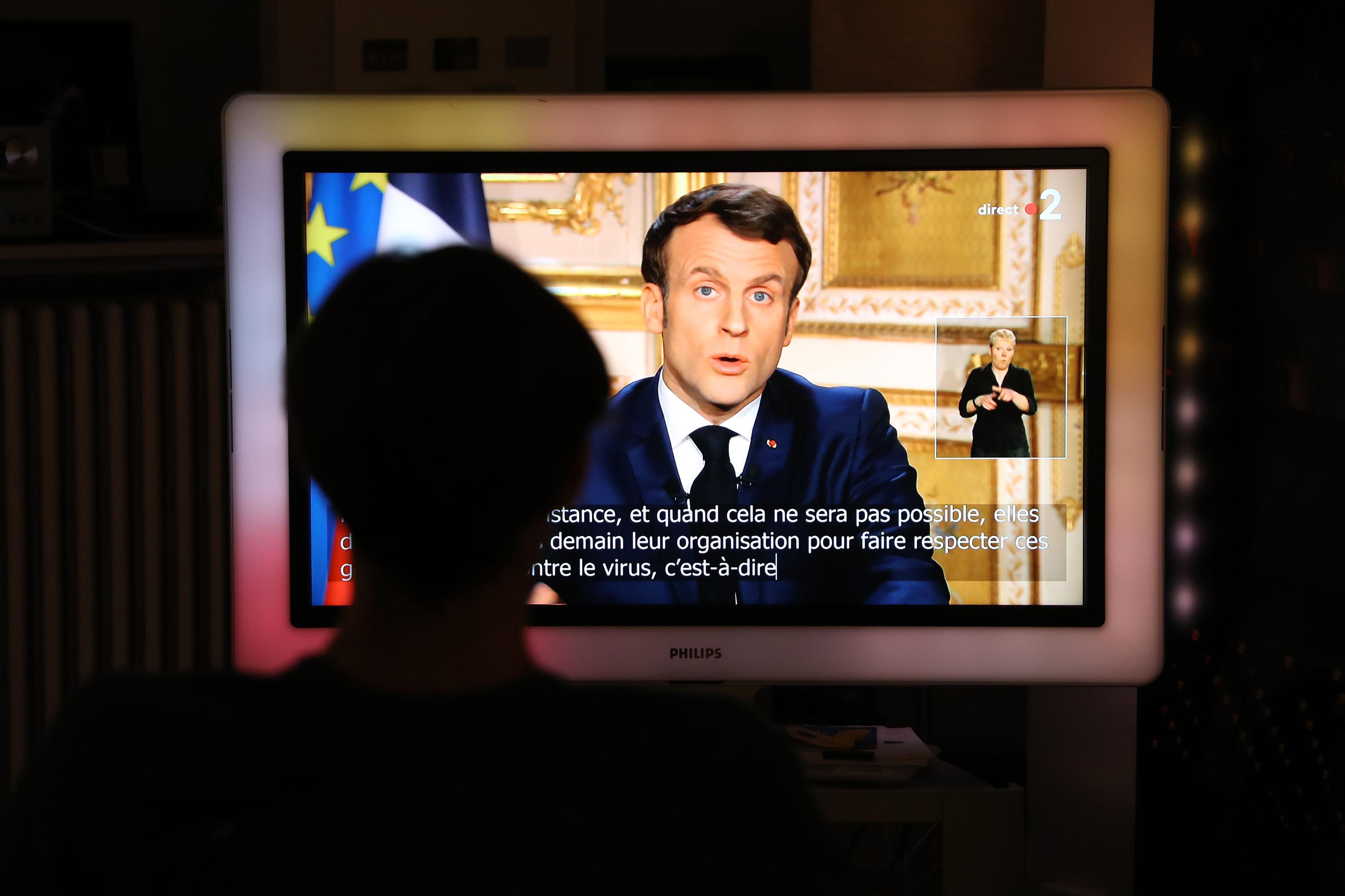 French President Emmanuel Macron is seen on a television screen on March 16 as he speaks during an address to the nation on the coronavirus outbreak.