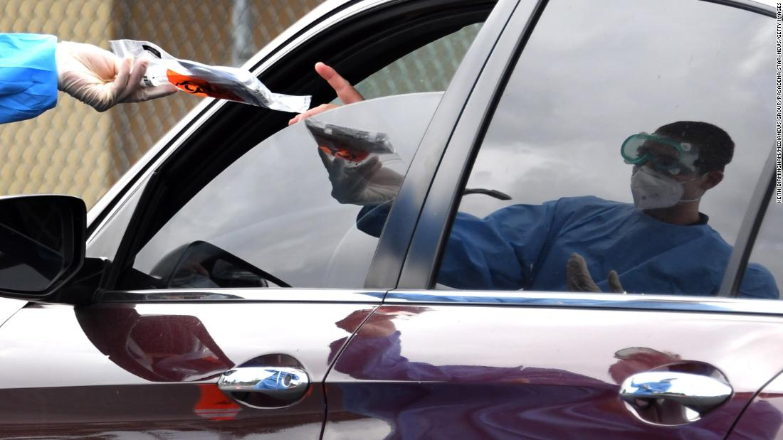 Lifeguard Jeremy Rocha gives a coronavirus test kit to someone at a drive-thru testing site in Long Beach, California, on April 18.