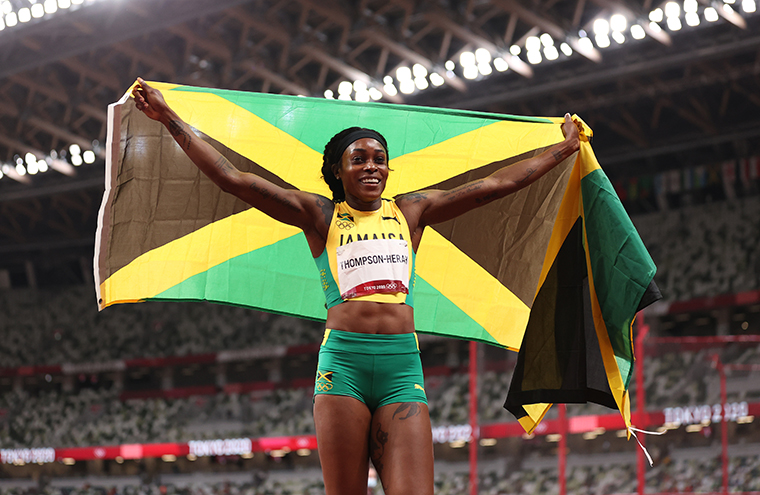 Elaine Thompson-Herah of Team Jamaica celebrates with her country's flag after winning the gold medal in the Women's 200m Final on day eleven of the Tokyo 2020 Olympic Games at Olympic Stadium on August 3, 2021.