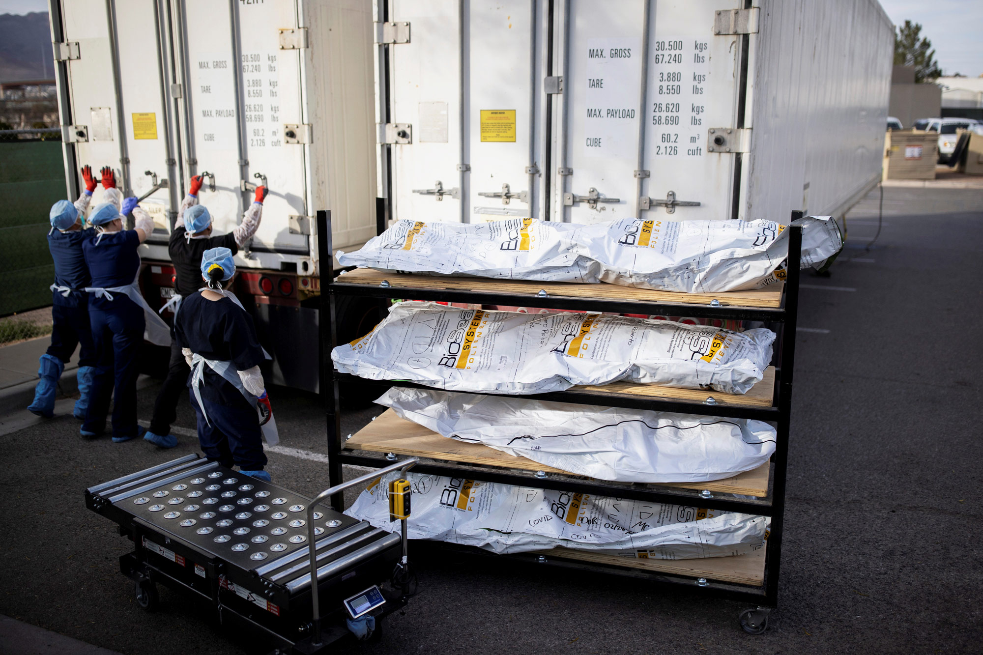Workers in El Paso, Texas, move coronavirus victims from refrigerated trailers into the main morgue on November 23.