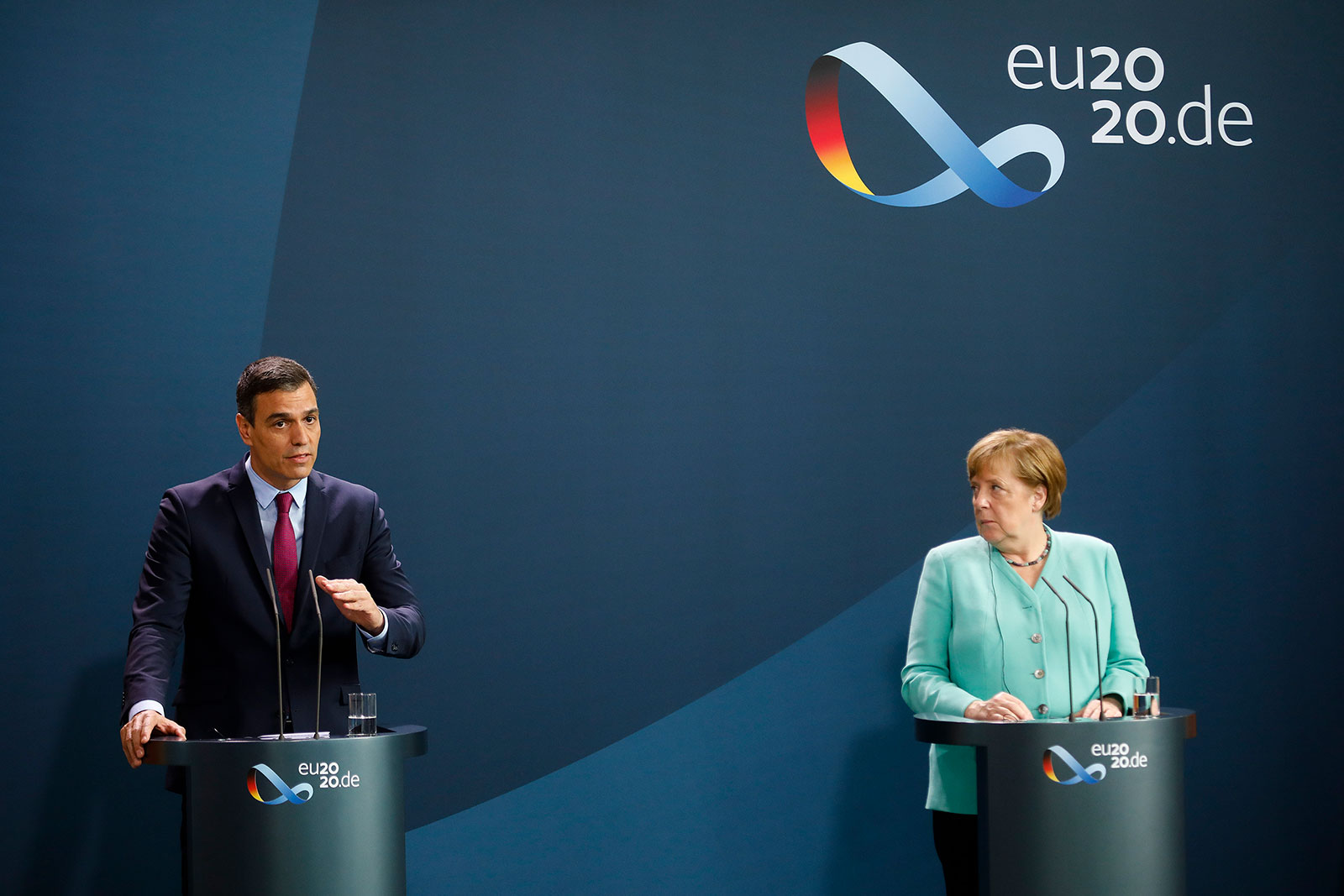 From left, Spanish Prime Minister Pedro Sanchez and German Chancellor Angela Merkel deliver a statement ahead of a meeting in Berlin, Germany, on Tuesday.