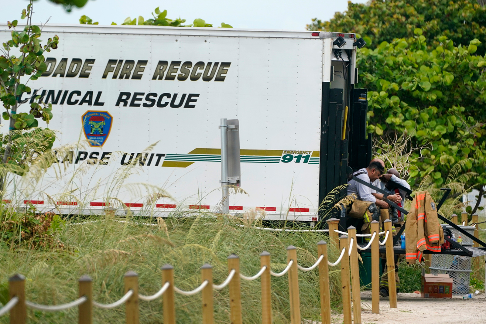 Firefighters wait in a truck near the site of a building that partially collapsed on Thursday.