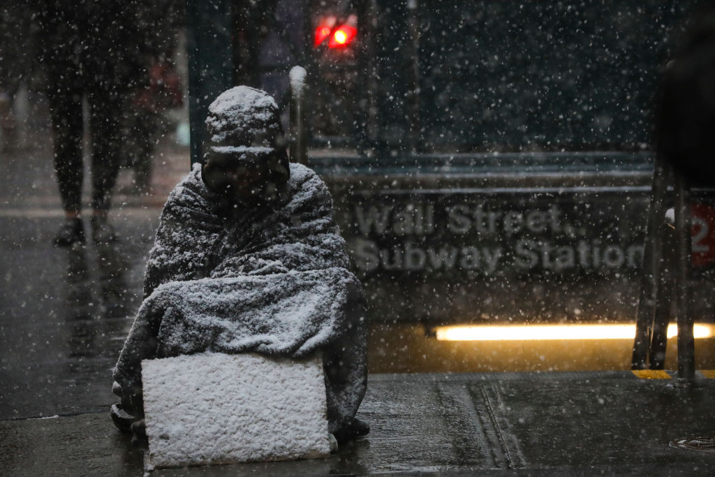 A homeless man sits in the falling snow in the Financial District on Jan. 30, 2019 in New York City.