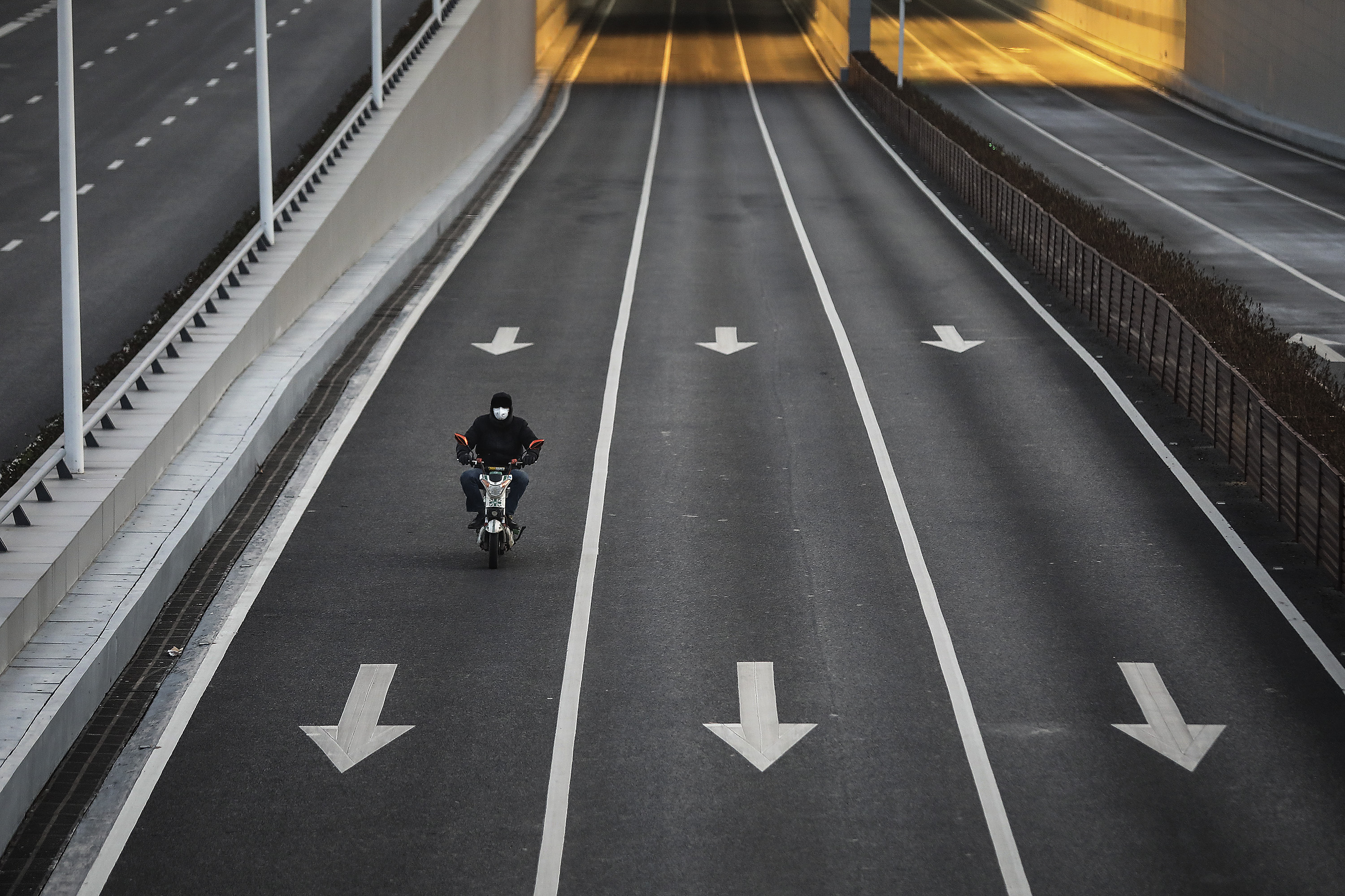 A man cycles on an empty street at Optical Valley in Wuhan, Hubei province, China.